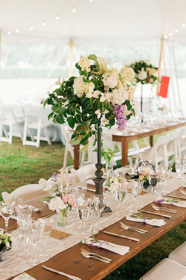 Tall vintage centerpiece set at top wood tables and tented reception | Seaside Eisenhower House Newport Wedding In Rhode Island | Photograph by Eileen Meny Photography  See the full story at http://storyboardwedding.com/seaside-eisenhower-house-newport-wedding/