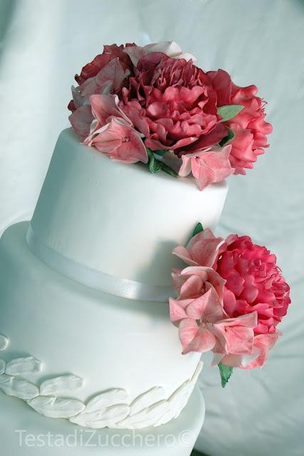 Testa di zucchero - torta decorata con fiori di zucchero in tonalità di rosa e rosso.  #cakedesign  Idee e strumenti per realizzarli su www.decorazionidolci.it