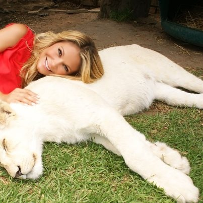 Beauty is in the eye of the beholder. Claudia cuddling with one of the white lion cubs at Lory Park