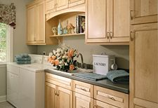 Maple cabinetry in a Natural finish makes for a clean, uncluttered, organized laundry room.  By KraftMaid Cabinets, available at Just Cabinets Furniture & More.