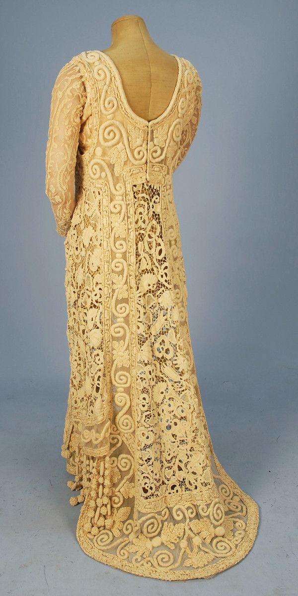 PARIS TRAINED HEAVY LACE GOWN, c. 1901. Cream 1-piece with long bobbin lace on net sleeve, open square neck and back, dress fashioned with panels of Irish crochet and net with padded ribbon embroidery in a pattern of scrolls and flowers, hem decorated with heavy cord fringe with knotted baubles, back closure.