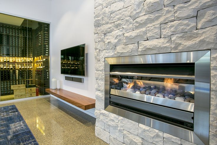 Stainless Steel modern gas fireplace in limestone cladding  Polished concrete flooring, glass wine cellar