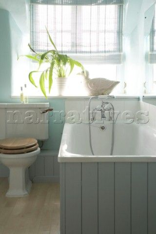 A traditional country bathroom in blue bath with tongue and groove wood panelling low cistern toi