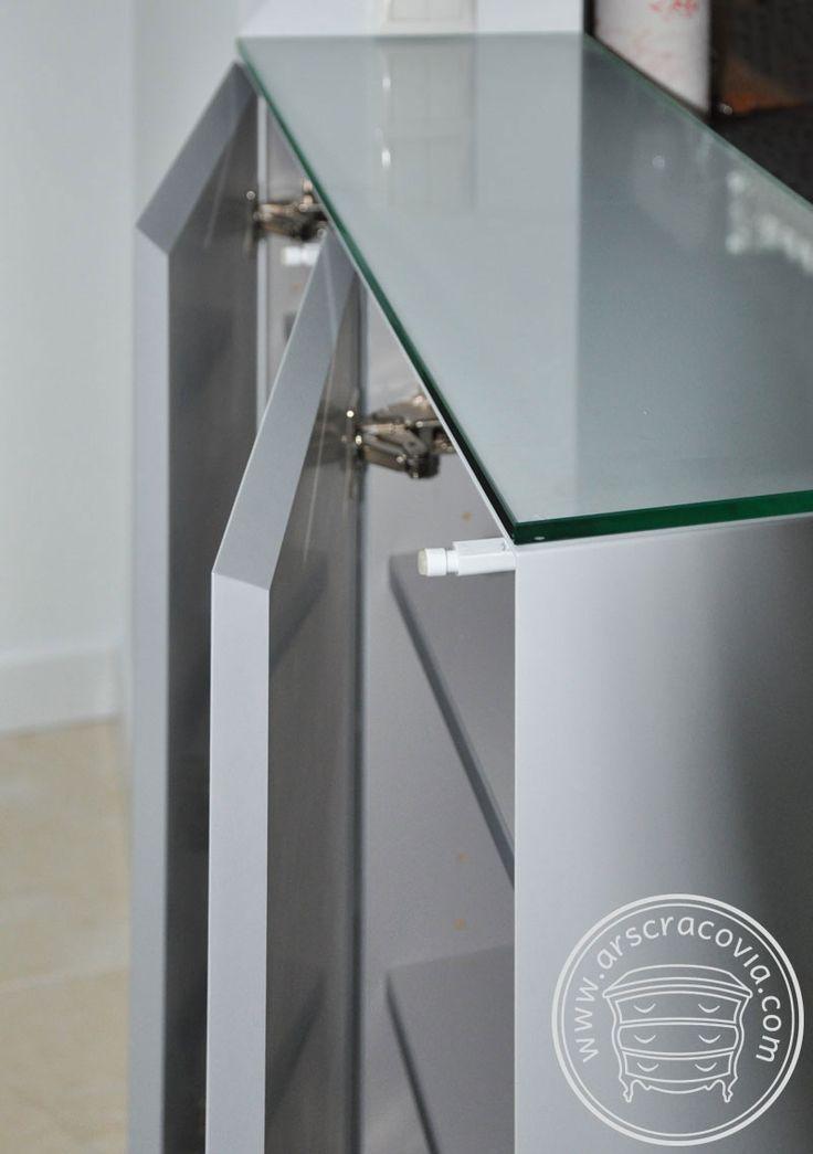 Na krótkim boku lady kuchennej ukryta szafka otwierana od strony jadalni, za pomocą mechanizmu tip-on. Fronty posiadają ścięte krawędzie dzięki czemu po zamknięciu tworzą jedna bryłę.