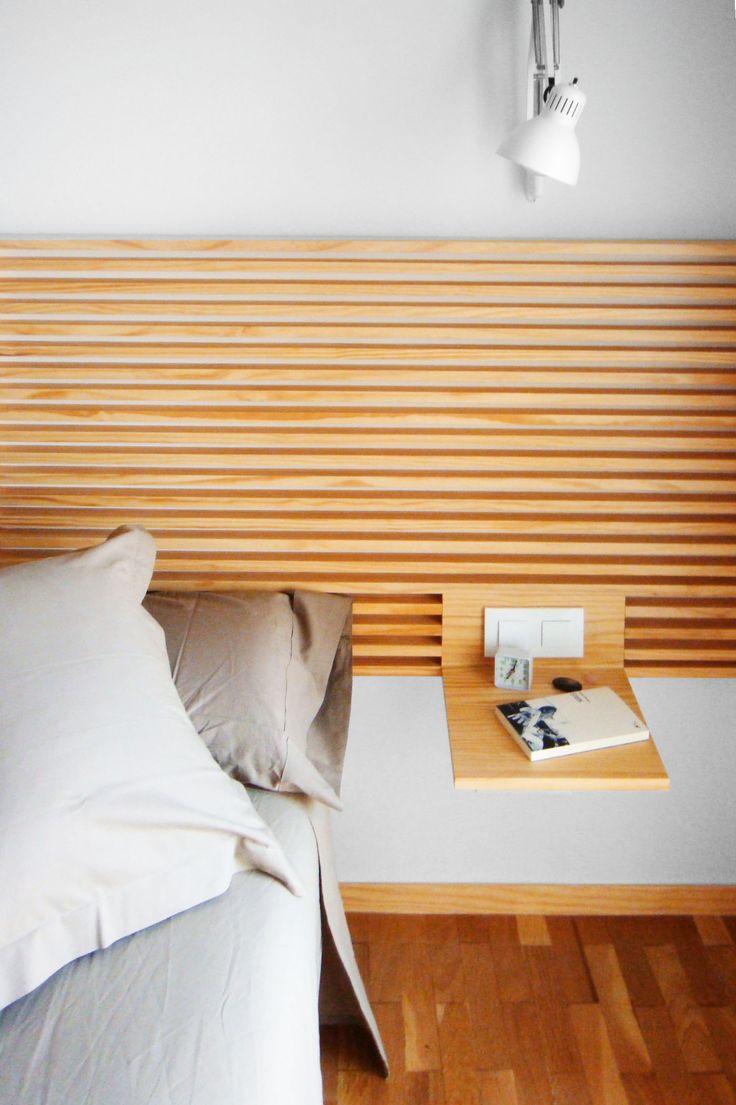 Detalle del cabecero de madera de la cama con mesilla e interruptores integrados. Diseño y reforma de 08023 Arquitectos - Barcelona