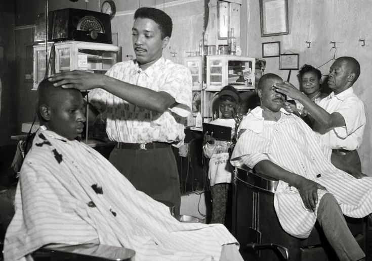 """Barbers Pete Boyd and Johnny Gator cut hair in Gator's barbershop circa 1950, while female relatives socialize in the background. Photo by Charles """"Teenie"""" Harris, via the Carnegie Museum of Art."""