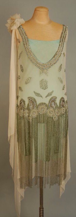 "JEWELED FLAPPER DRESS with BEADED FRINGE, 1920's. White chiffon with deep ""U"" neckline front and back trimmed with a wide band of pearl, rhinestone and crystal bead medallions, wide jeweled hip band with graduated long beaded fringe"