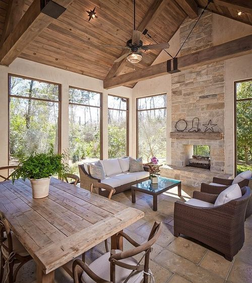 Neutral sunroom, fire, stone, beams.