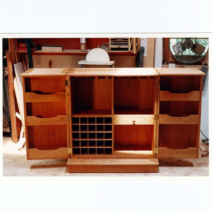 this is a large liquor cabinet on casters with double doors that open fully and allows the top to fold out for a 6 foot by 2 foot bar top
