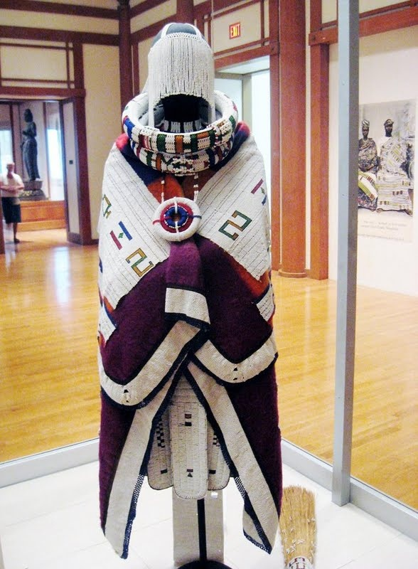 "Africa | The Ndebele Bridal Ensemble from the 20th Century from the Front | ""Ndebele brides' beaded attire includes a richly embroidered blanket; a bridal apron; a beaded veil; a neck ornament; neck, arm, and leg rings; and a distinctive train. On their wedding day, brides receive a grass broom with a beaded handle, alluding to their new domestic duties. In older works, such as the train, white beads predominate and geometric motifs are delicate."""