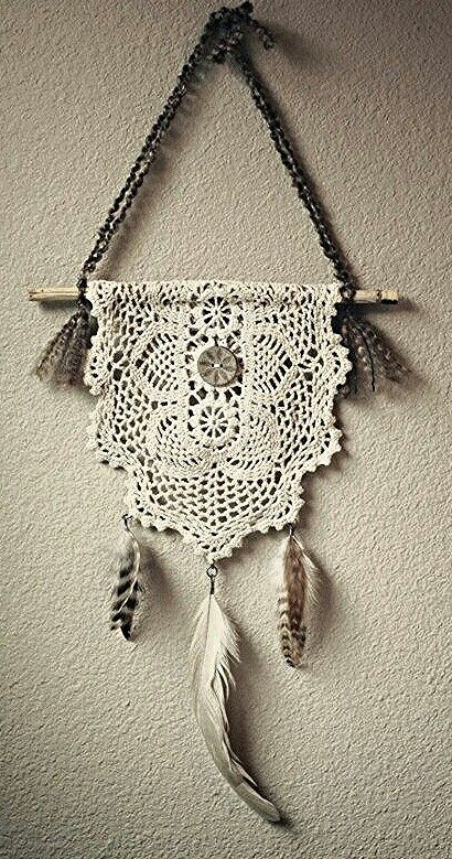 Simple. I am not a fan of the feathers, but a doily hung over a stick is pretty cool for wall art