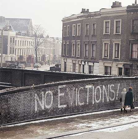 Two women walking past the graffiti 'No Evictions!' on a railway bridge on Grafton Road, Camden. Much of the area was bulldozed and redeveloped in the 1960s and early 1970s.