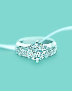 unique Tiffany's round shaped wedding engagement ring with a shared-setting diamond band #OnlineDiamondStores