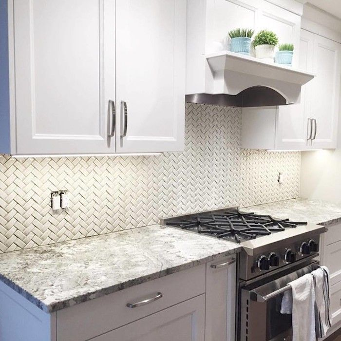 Pastel Blue And White Cabinets With Silver Metal Handles Inside A Kitchen W In 2020 Kitchen Backsplash Designs Herringbone Tiles Kitchen Subway Tile Backsplash Kitchen