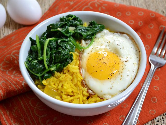 Golden Rice Bowls  2 Tbsp butter  1 small yellow onion  2 cloves garlic  2 cups uncooked jasmine rice 1 tsp turmeric  ½ tsp ground cumin  ⅛ tsp cinnamon  1 whole bay leaf  3 cups veggie broth 2 Tbsp olive oil  2 cloves garlic  1 (16 oz.) bag spinach  to taste salt & pepper  6 large eggs