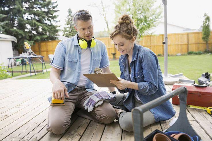 Couple with clipboard preparing to sand backyard deck - Hero Images/Getty Images