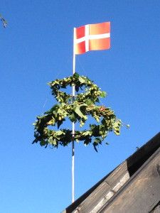 Rejsegilde: the Danish tradition when building a house or shed is to have a small celebration before the roof comes on. You put a double wreath and the flag at the gable of the construct like in the photo.
