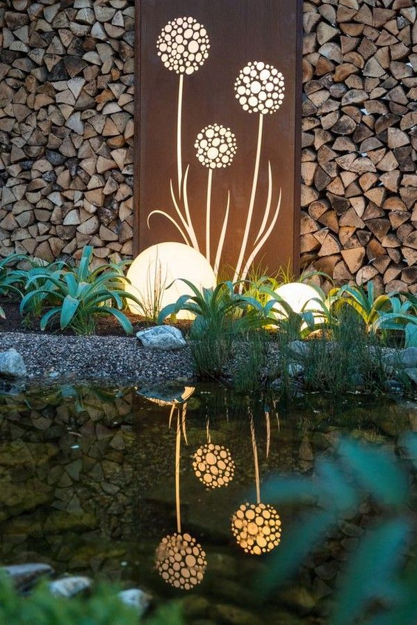Plasma cut scrap metal sculpture, doubling as wood rack and reflective feature!