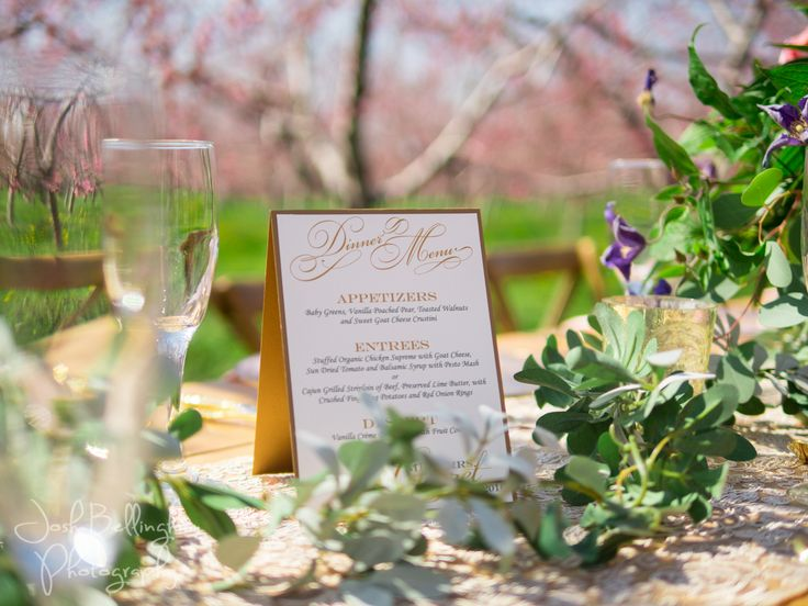 Gorgeous details of wedding menu created by Charmed Occasions in Niagara, Canada. Beautiful gold and white and blush colors for a wedding reception in an Orchard. Stunning Table decor with lush flowers. @pambocb @niunia1977 @WarehouseNOTL @constellationev @orchardcroft  #JoshBellinghamPhotography