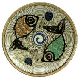 Pictata in culorile specifice ceramicii smaltuite de Horezu, pe fond alb fildes si infrumusetata cu model zoomorf - pesti, dar si geometric in nuante de albastru, verde, maro si portocaliu, aceasta farfurie surprinde perfect stilul unic si irepetabil al mesterilor populari ce prelucreaza lutul din Horezu.(Ceramic plate of Horezu)