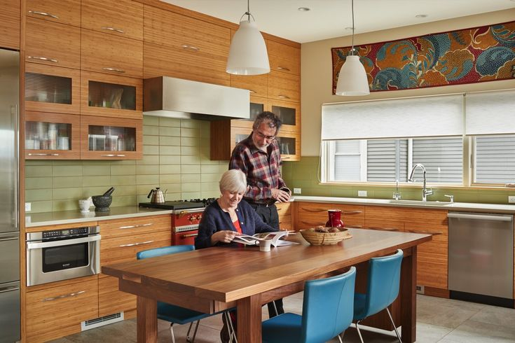 "Pat Ramsey and Olivier Carduner relax in the kitchen of their LEED Gold-certified home, designed by architect Patricia Brennan and built by Toth Construction, with LEED guidance from O'Brien & Company. ""We love to cook, and we have a lot of family,"" says Carduner. ""We needed a place for three cooks at the same time."" The custom table and bamboo cabinetry are by Jonathan Pauls, Inc. (Benjamin Benschneider/The Seattle Times)"