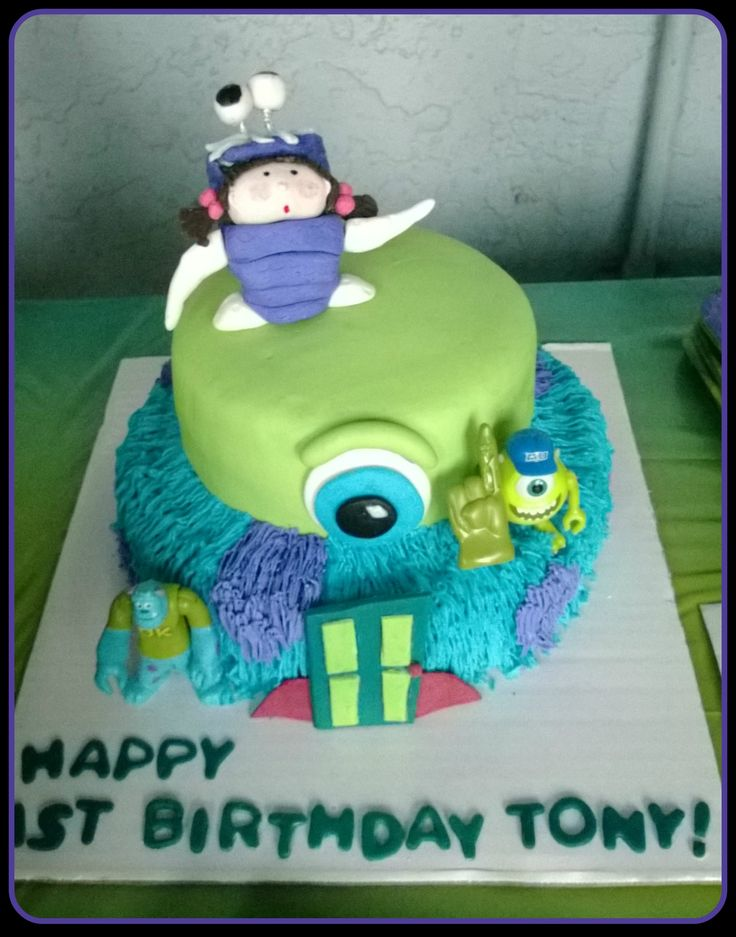 """Monsters Inc. Birthday cake I made!  It's a rich chocolate cake with a chocolate ganache center. The """"Mike Wazowski layer is covered in a marshmallow fondant and """"Sully's"""" layer is decorated with buttercream. I made Boo with some extra fondant, along with the eye, and the door as well! I was very happy with the results!:)"""