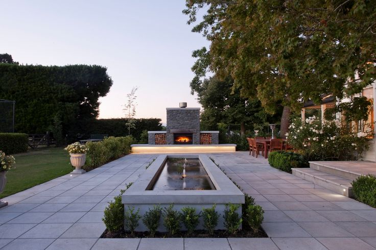 Peaceful water feature framed with luscious vegetation to break up and soften the majority concrete area.