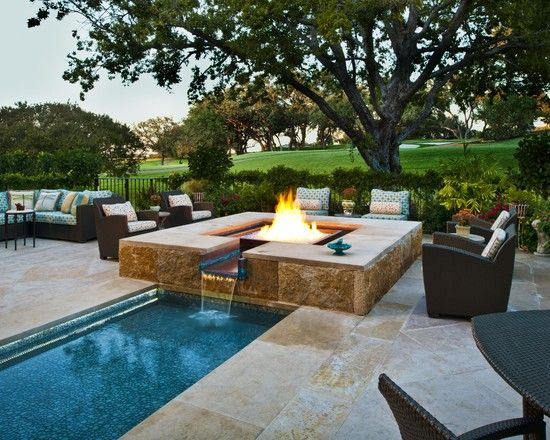This water feature and teal diamond glass firepit sit at the back of the property. The molded copper water basin gently spills into a rill that is lined with pebble glass tile to echo that of the main pool. The rill is equipped with LED lighting.