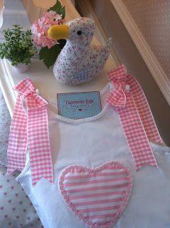 Camiseta blanca de sisas con corazón de rayas rosa y blanco, con dos lazotes en los hombros.