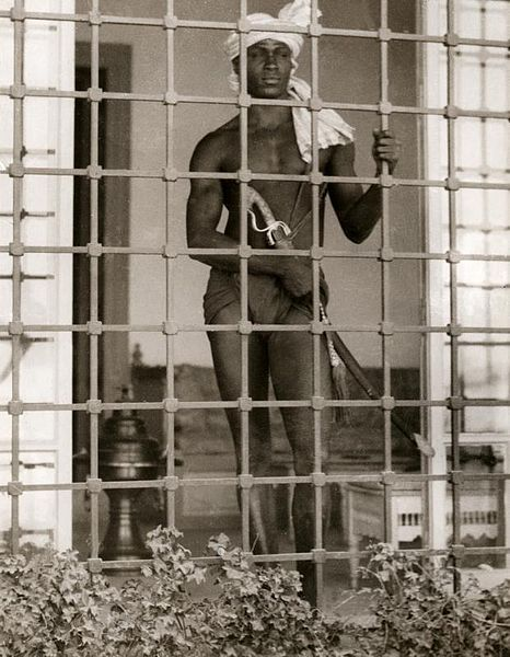 Black Eunuch in a turban with rifle behind a gate in 1931 Tunis guarding a harem. photo courtesy of Recuerdos de Pandora