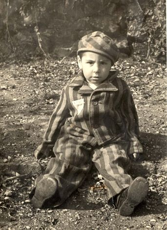 Auschwitz, Poland, A boy wearing a prisoners uniform after liberation, 1945. A triangular badge with a number is sewn to the uniform.