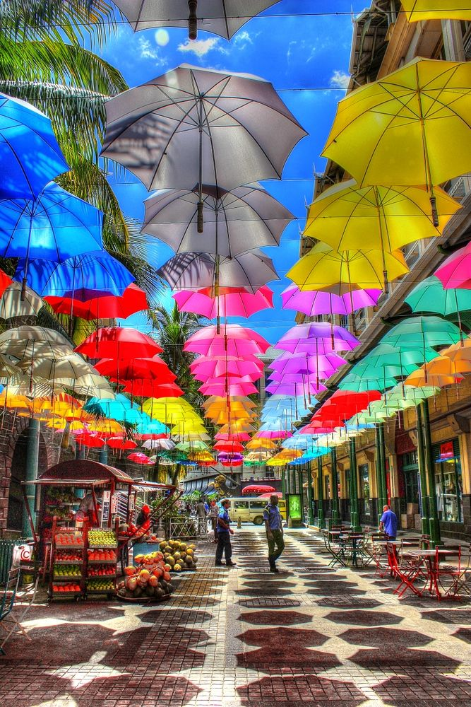 Le Caudan Waterfront in Port Louis - a great place to shop and eat! These colourful umbrellas create shade along the walkway. #portlouis #lecaudanwaterfront #beautiful-- Tanks that Get Around is an online store offering a selection of funny travel clothes for world explorers. Check out www.tanksthatgetaround.com for funny travel tank tops and more travel bucket list inspo.