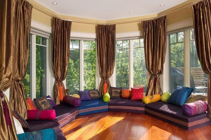 canapé modulable en bleu et pourpre, coussins multicolores à motif éléphant et rideaux marron