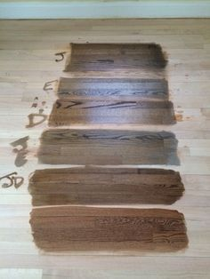 Minwax Color Guide. Stain samples on a white oak floor. From top: Jacobean, Ebony, Dark Walnut, 50/50 Jacobean and Ebony, 50/50 Jacobean and Dark Walnut, and English Chestnut at the bottom. We went with 50/50 Jacobean and Dark Walnut and love it! It's hard to describe colors, but if I worked for Miniwax Color Naming Dept., I would call it Pecan.