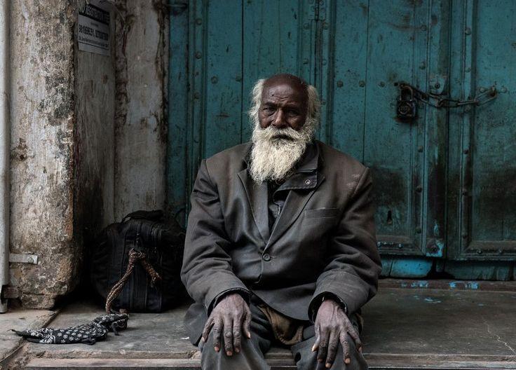 Ein Obdachloser sitzt im indischen Neu-Delhi auf einer Stufe. Seine gesamten Habseligkeiten passen in die Tasche neben ihm.