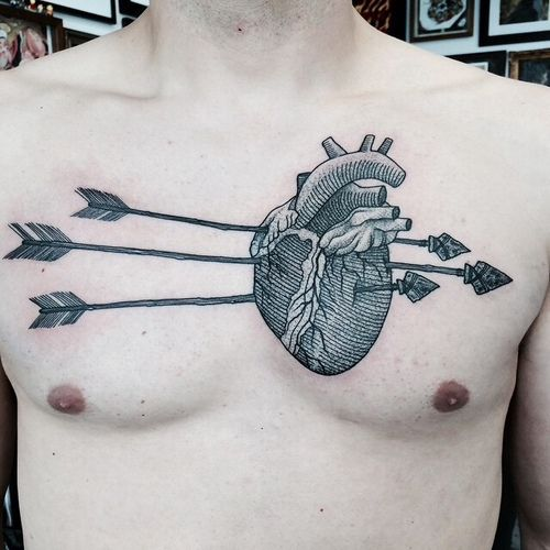 Black linework illustration-style anatomical heart pierced by three arrows tattoo