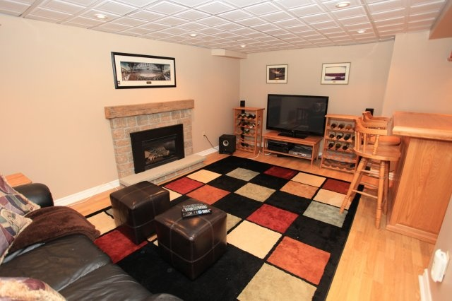 "Cozy ""man cave/home theatre"" rec room complete with gas fireplace, solid oak bar and 2 piece washroom with roughed-in piping for shower."