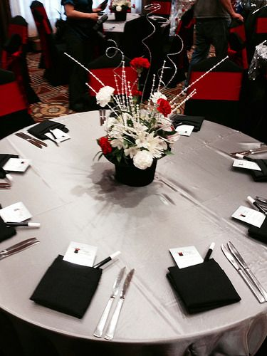 Magic themed event, complete with a top hat floral centerpiece on silver matte satin linens, black linen napkins, and magician-like accessories. | At the Crowne Plaza West in Plymouth, MN