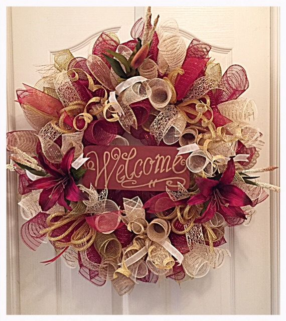 You will enjoy greeting all you family and friends when you hang up your WELCOME Burgundy Lily Deco Mesh Wreath.  It is made with high quality Burgundy, Cream, Moss and Burlap deco mesh.  There are silky burgundy ribbons, gold lacey ribbons, cream ribbons and gold diamond ribbons.  It shows with burgundy lilies, fox tails and glittered gold/cream picks with gold flex tubing.  The WELCOME sign is made from wood- hand painted burgundy and gold.  This wreath measure 25 inches and can ship out…