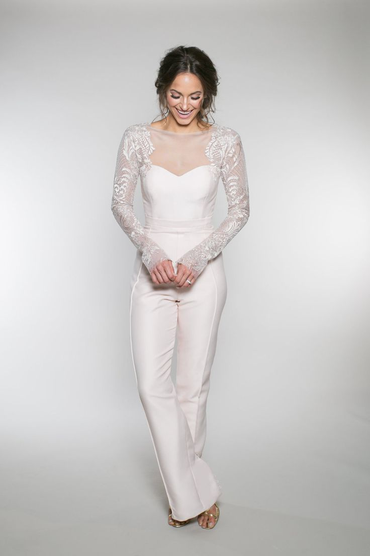 """The """"wedding pant suite"""" features an illusion long sleeve bodice with a pin tuck pant. The back of the pant has functioning covered buttons allowing the bride to reveal as little or as much skin as she wants. * Photographed In: Blush / Silver * Color Options: Off-White / Silver, B"""