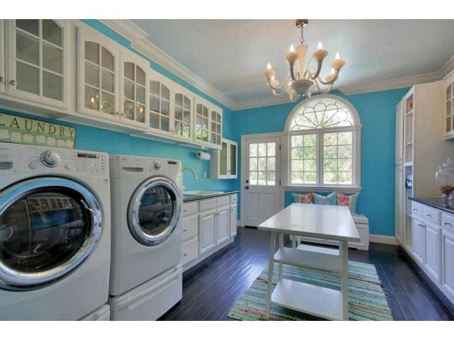Fancy laundry room. Even has a chandelier. Pretty blue color on the wall with lots of natural light.