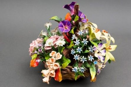 Refined basket centerpiece thousand-flowers (petunias, roses, anemones, daisies, lilies and meadow flowers) worked in fine Capodimonte porcelain. Each flower is reproduced in detail by the artist and it is then laid on an elegant basket, which is also entirely woven by hand.        Dimensions cm. 23x22