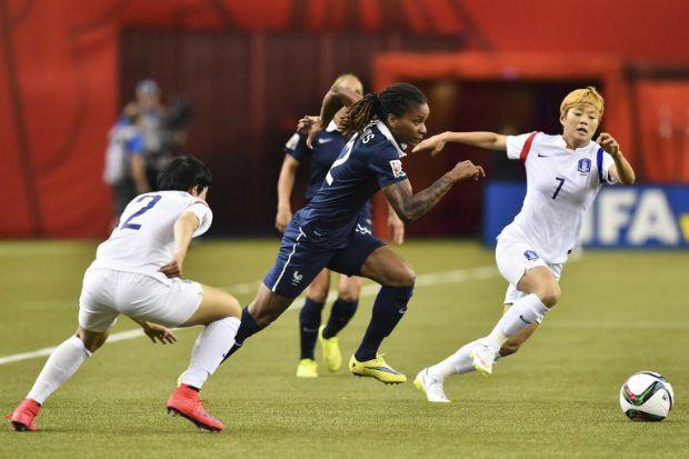 La française Élodie Thomis à l'attaque entre deux joueuses coréennes, dimanche 21 juin 2015. (NICHOLAS KAMM / AFP)