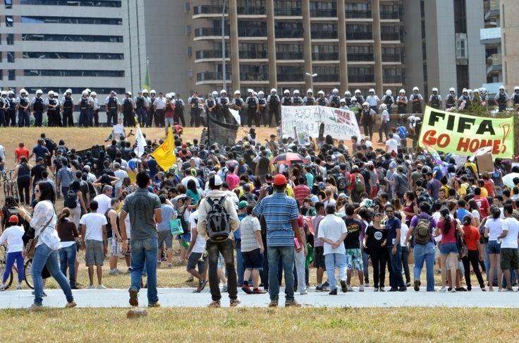 7.set.2013 - Observados por policiais militares, manifestantes de várias entidades e movimentos sociais levatam cartazes enquanto deixam a Esplanada dos Ministérios, na manhã deste sábado (7), onde foi realizado o tradicional desfile do Sete de Setembro. Eles seguiram em protesto para o Estádio Nacional Mané Garrincha