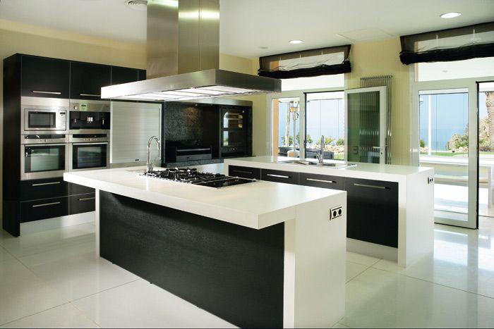 Outra opção é optar pelo básico e ficar com cores neutras, como essa bancada de cozinha em silestone branco, com coifa em ilha, um modelo recorrente em projetos espaçosos