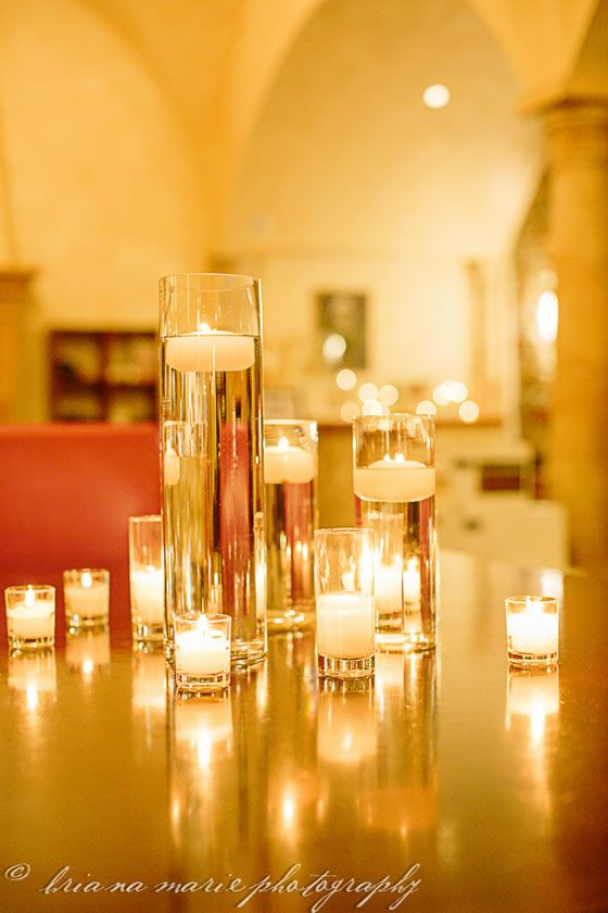 DIY wedding decor: Tall cylinder vases, filled with water, topped with floating candles. Gives off warm and inviting light. Creates welcoming atmosphere. (Provides entertainment for all your pyromaniac friends ;)