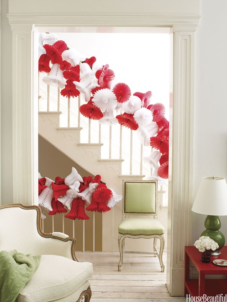 Banisters can be tricky to decorate. For a light, airy, and cheerful look, try stringing red and white paper bells together with fishing line. (Tip: Get creative with your decorations. We found these at a wedding supply store!)   - HouseBeautiful.com