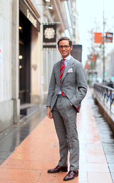 Light grey suit, light blue shirt with white collar, red stripe tie