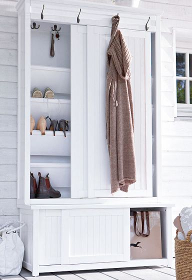 Shoe rack behind the sliding doors of the white wardrobe with the lower part ideal for boot storage