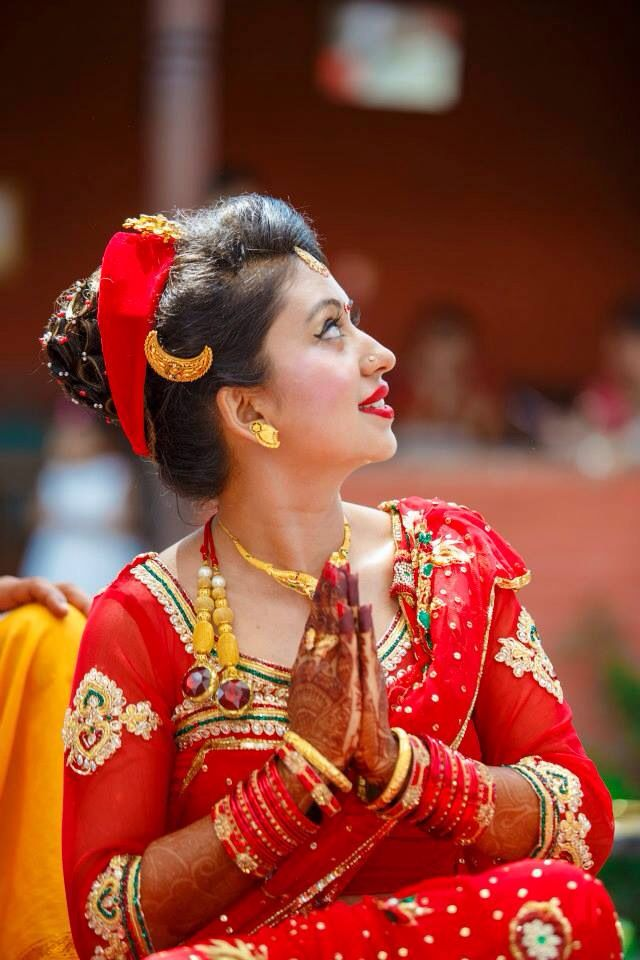 A Hindu Nepali bride in her ceremonial attire, paying respect to the Sun believed to be a form of God according to Hindu Mythology